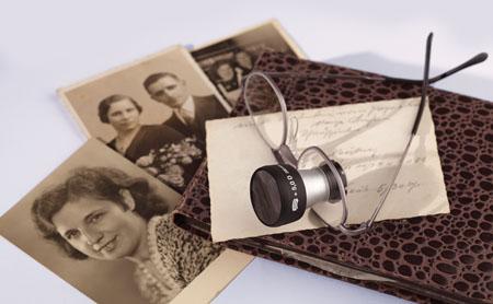 Brille mit Fernrohrsystem und alten Bildern