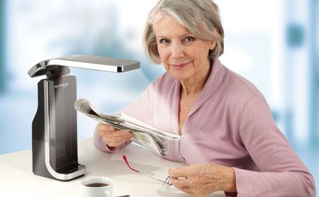 Frau mit LowVision Leuchte liest Zeitung